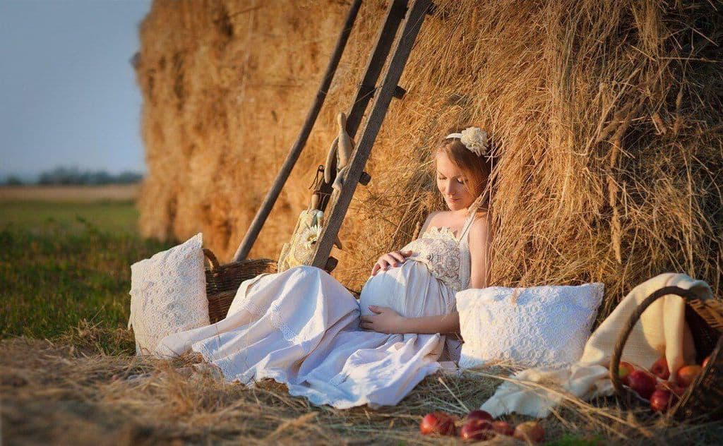 Беременная девушка на сеновале