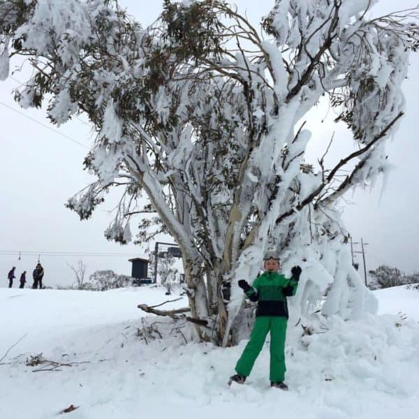 Подросток под деревом в снегу